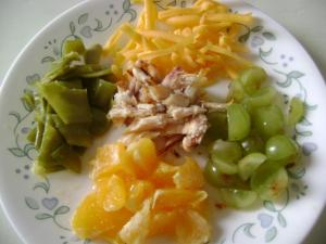 Soft cooked green beans, cheese, quartered grapes, chopped orange,  and shredded chicken makes a good finger food lunch.