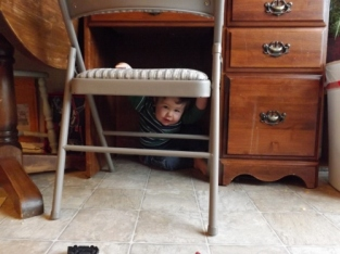 Under a desk with the chair pulled in.